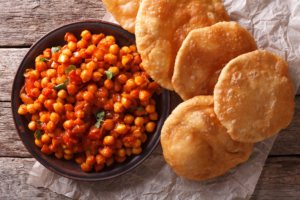 Delicious Indian Chana masala and puri bread close-up on the table.
