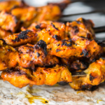 Freshly grilled chicken tikka masala kebabs on skewers dripping onto a piece of naan flatbread cooked in a Tandoori oven.