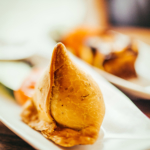 Two white plates containing freshly made samosas, a favorite of Indian cuisine.